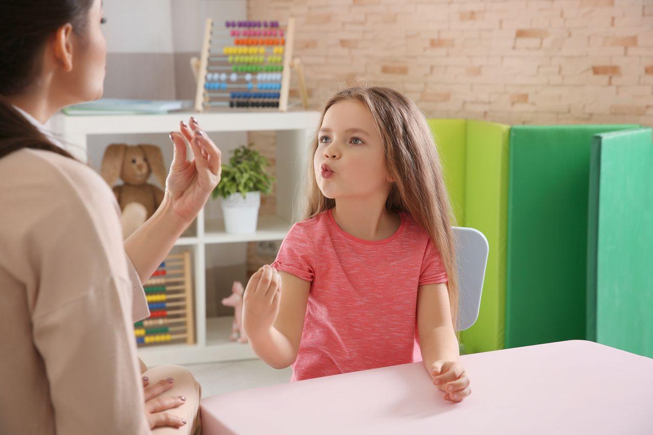 Uma criança sendo treinada por uma fonoaudióloga a treinar a pronúncia de palavras